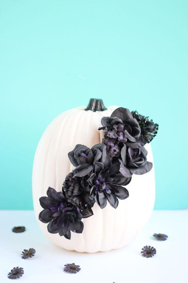 """<p>What's black and white and wickedly chic all over? This pretty pumpkin centerpiece, which will steal the show on your dining room table. </p><p><strong>Get the tutorial at <a href=""""https://designimprovised.com/2017/10/pumpkin-week-black-flower-pumpkins.html"""" rel=""""nofollow noopener"""" target=""""_blank"""" data-ylk=""""slk:Design Improvised"""" class=""""link rapid-noclick-resp"""">Design Improvised</a>. </strong></p><p><strong><a class=""""link rapid-noclick-resp"""" href=""""https://www.amazon.com/Luyue-Vintage-Artificial-Flowers-Decoration/dp/B081RB8P5N/ref=sr_1_2?tag=syn-yahoo-20&ascsubtag=%5Bartid%7C10050.g.3739%5Bsrc%7Cyahoo-us"""" rel=""""nofollow noopener"""" target=""""_blank"""" data-ylk=""""slk:SHOP SILK FLOWERS"""">SHOP SILK FLOWERS</a><br></strong></p>"""