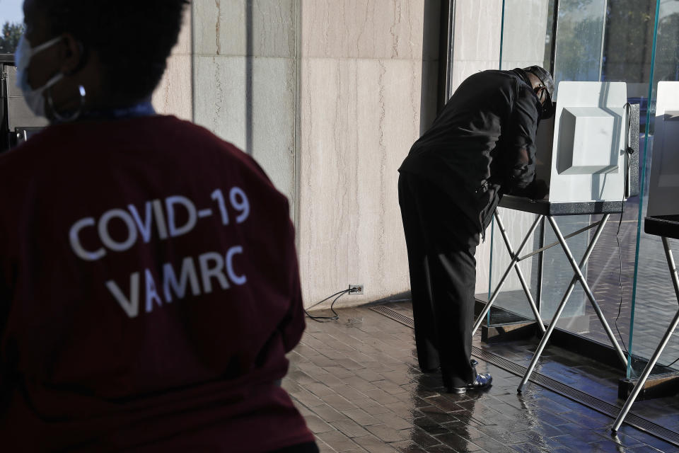 A Virginia Medical Reserve Corps member waits to clean a booth as a voters cast their ballot on Election Day at Hampton City Hall Tuesday Nov. 3, 2020. (Jonathon Gruenke /The Virginian-Pilot via AP)