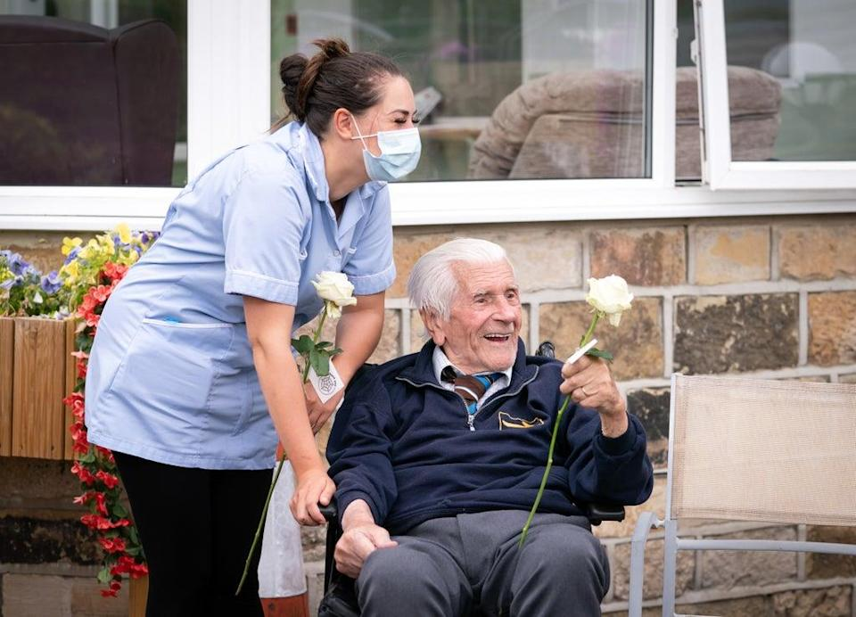 """Health care assistant Rose Waddington and 98-year-old resident John Kykot with """"thank you"""" white roses that were presented to them at Norwood House Nursing Home in Keighley, Yorkshire (Danny Lawson/PA) (PA Wire)"""