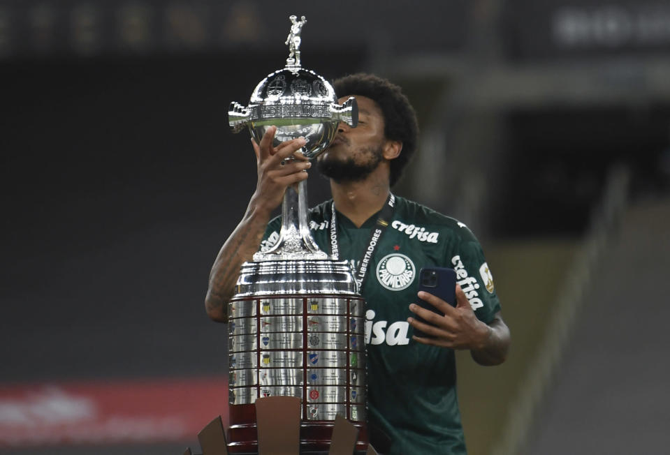 Luiz Adriano of Brazil's Palmeiras kisses the trophy after winning the Copa Libertadores final soccer match against Brazil's Santos at the Maracana stadium in Rio de Janeiro, Brazil, Saturday, Jan. 30, 2021. Palmeiras won 1-0. (Mauro Pimentel/Pool via AP)