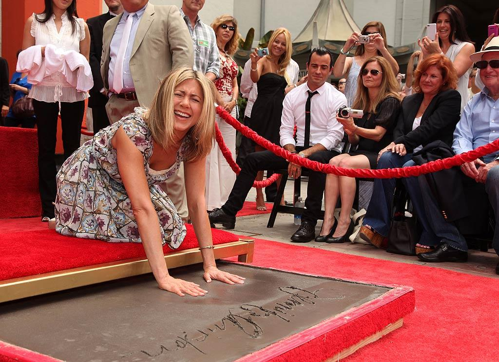 "Jennifer Aniston's new beau, actor Justin Theroux, looked on as his lady love slapped her hands into wet cement during her Hand and Footprint Ceremony on the Hollywood Walk of Fame. Eric Charbonneau/<a href=""http://www.wireimage.com"" target=""new"">WireImage.com</a> - July 7, 2011"