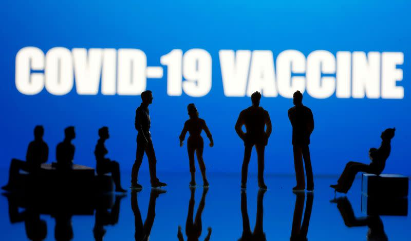 FILE PHOTO: Small toy figures are seen in front of a Covid-19 Vaccine logo in this illustration taken