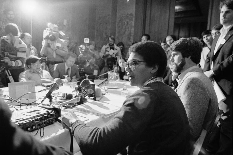 Anita DeFrantz, of Princeton, N.J., a member of the Olympic rowing team and of the Olympic Advisory Council, talks to members of the media at a news conference in Colorado Springs April 11, 1980. At her right is Peter Schnugg a member of the U.S. water polo team from Orinda, Calf. They discussed the athlete's view concerning a possible Olympic boycott. (AP Photo/Ed Andrieski)