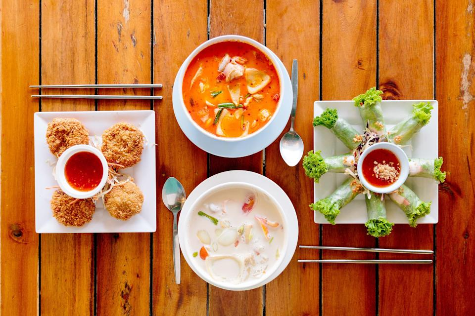 Tom Yum soup and fresh spring rolls (among other dishes) are placed on a wooden table alongside chopsticks and spoons