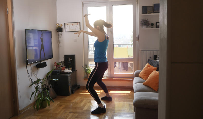 Woman exercising and watching online workout video
