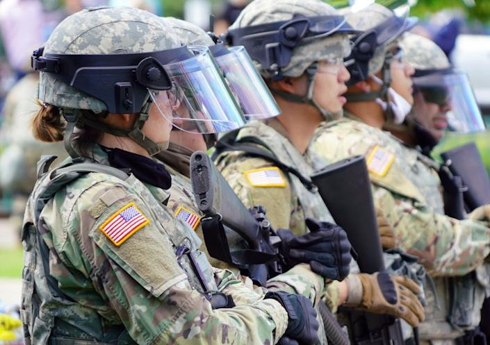 Minnesota State Police and National Guard keep watch after a night of riots and looting in Minneapolis. Protests continued across the nation Friday night.