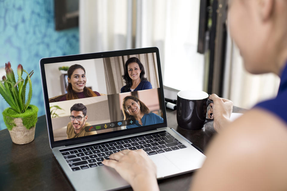 Women attending business video call meeting using laptop at home
