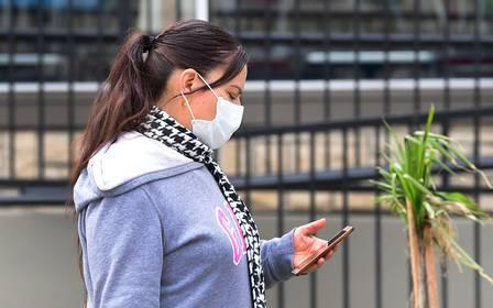 87587926_A woman checks her cellphone while wearing a facemask in Los Angeles on March 20 2020 a day (1).jpg
