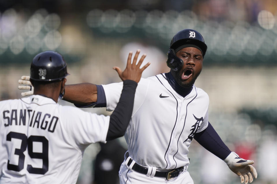 Detroit Tigers' Akil Baddoo, right, is greeted by first base coach Ramon Santiago after hitting a walk-off single during the tenth inning of a baseball game against the Minnesota Twins, Tuesday, April 6, 2021, in Detroit. (AP Photo/Carlos Osorio)