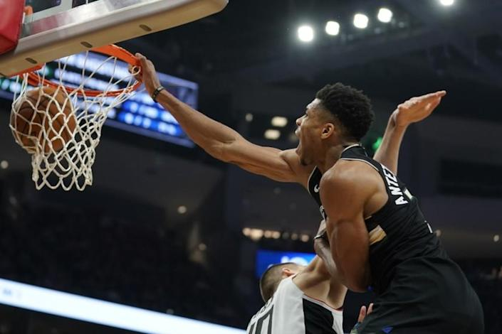 Milwaukee Bucks' Giannis Antetokounmpo dunks 0ver Los Angeles Clippers' Ivica Zubac during the second half of an NBA basketball game Friday, Dec. 6, 2019, in Milwaukee. (AP Photo/Morry Gash)