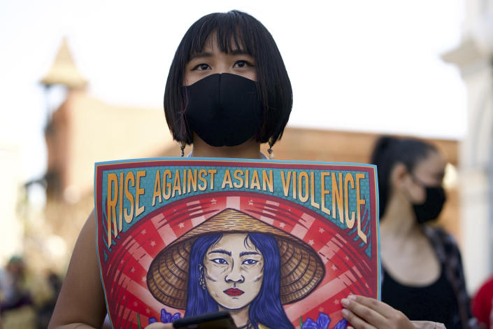 Ally Vega holds a poster by artist Pauline Cuevas, as she joins a rally against Asian hate crimes in El Pueblo de Los Angeles, Los Angeles Plaza Park, Saturday, March 27, 2021. Asian Americans and their allies held rallies Saturday in California, home of the nation's largest Asian population, to denounce shootings at massage businesses in Georgia and racism, xenophobia and misogyny. The gathered crowd demanded justice for the victims of the Atlanta spa shooting and for an end to racism, xenophobia and misogyny. (AP Photo (AP Photo/Damian Dovarganes)