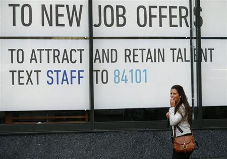 A woman walks past a recruitment agency in central London