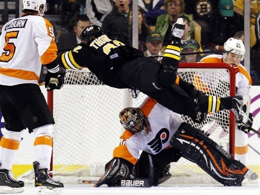 Boston Bruins' Shawn Thornton (22) trips over Philadelphia Flyers goalie Ilya Bryzgalov in the third period during an NHL hockey game in Boston, Saturday, March 17, 2012. Thornton was called for goalie interference. The Bruins won 3-2 in a shootout. (AP Photo/Michael Dwyer)
