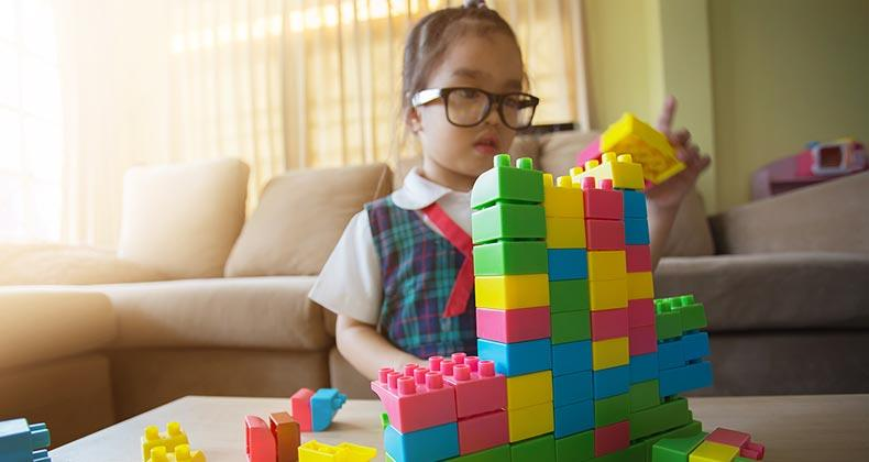 Little girl playing with building blocks in family room | Casezy idea/Shutterstock.com