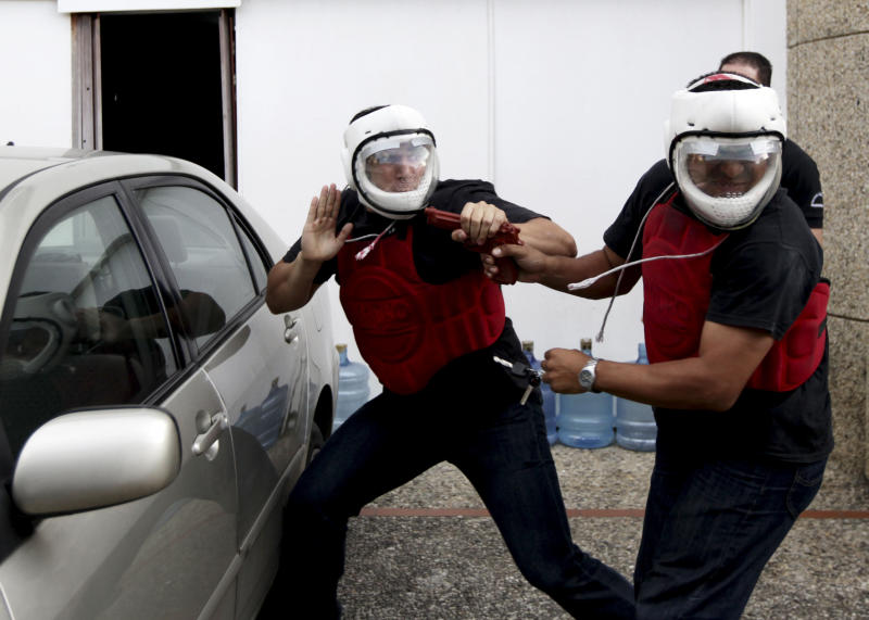 In this photo taken on Wednesday, May 30, 2012, a student, left, practices how to defend himself against a carjacking at a privately-run school in Caracas,Venezuela. The government says more than 14,000 people were killed in Venezuela last year, giving the country a murder rate of 50 per 100,000 people and making it one of the most violent countries in Latin America and the world. The murder rate has more than doubled since 1998, when Venezuela's President Hugo Chavez was first elected. (AP Photo/Fernando Llano)