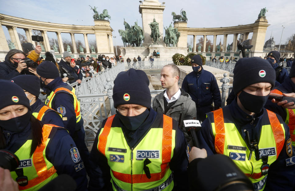 Aron Ecsenyi, center right, the protest organizer, stands behind a police line while his ID is checked in Budapest, Hungary, Sunday, Jan. 31, 2021. Protesters gathered at a central square in Hungary's capital of Budapest on Sunday demanding a rethinking of the country's lockdown restrictions. As the lockdown limiting restaurants to take-away service approaches the three-month mark, many business owners complain that they have received little to none of the government's promised financial assistance while other businesses like shopping malls and retail stores have been permitted to remain open. (AP Photo/Laszlo Balogh)