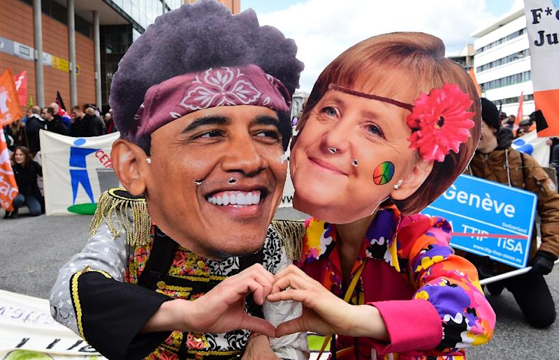 Protesters wearing masks featuring German Chancellor Angela Merkel and US President Barack Obama pose during a prostest rally on the eve of Obama's vist to Hannover