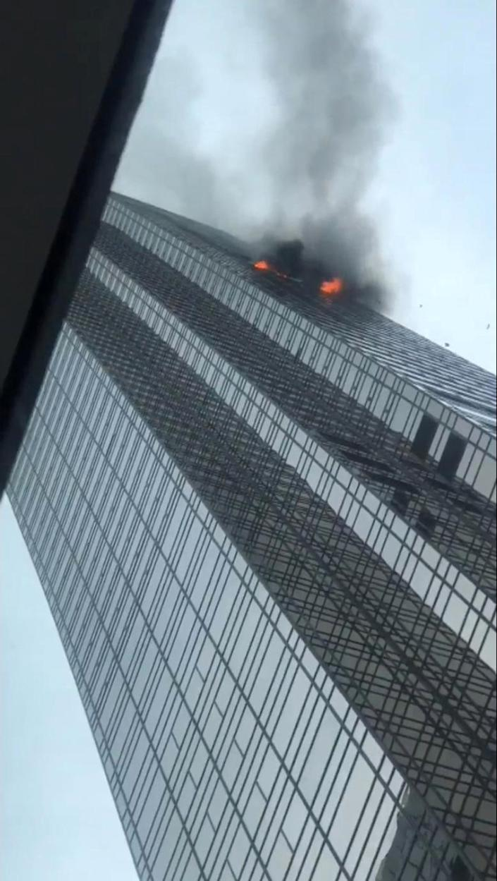 <p>Debris falls during a fire at Trump Tower in New York, April 7, 2018 in this still image from video obtained from social media. (Photo: Twitter@ZionLee_ /via Reuters) </p>