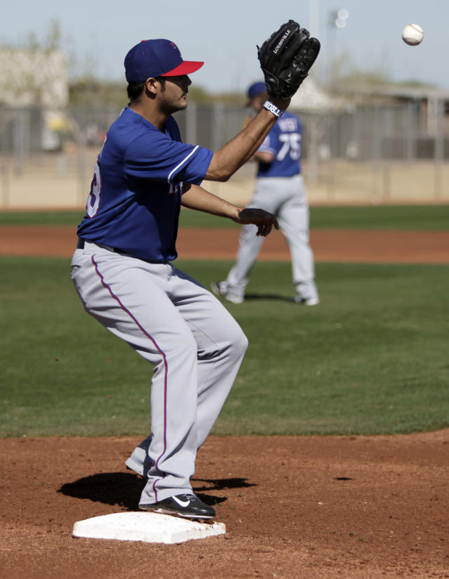 Texas Rangers' Martin Perez (33) reaches out for the throw as he covers first in fielding practice during spring training baseball practice, Monday, Feb. 17, 2014, in Surprise, Ariz. (AP Photo/Tony Gutierrez)