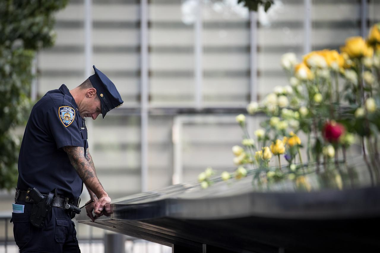 An New York City Police Department officer is accused of assaulting a man over a spilled drink. In this photo, a New York City Police Department (NYPD) officer pauses while visiting the North pool during a commemoration ceremony for the victims of the September 11 terrorist attacks at the National Sept. 11 Memorial, September 11, 2017 in New York City.