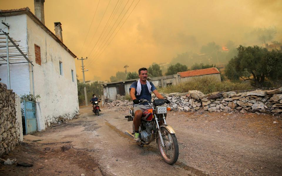Locals evacuate as fire advances on the village of Cokertme in Bodrum, Turkey - Emre Tazegul/AP