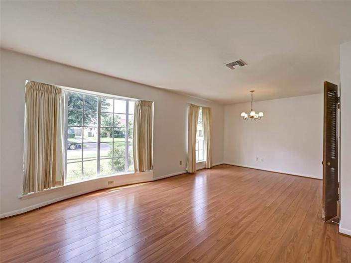 the empty living space with laminate floors and two windows in a house for sale in houston