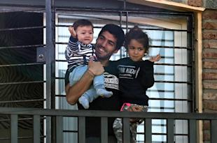 Luis Suarez holds his children Benjamin and Delfina as he greets fans. (AFP)