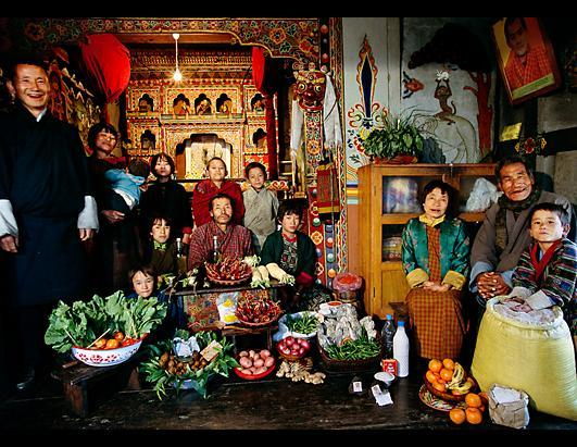 """The Namgay family in their prayer room with a week's worth of food in Shingkhey, Bhutan. The family spend $5.03 a week on groceries. They cook with a clay stove fueled by wood fire, and preserve food by drying. """"The Hungry Planet"""" documents families around the world with their weekly food purchases, exposing global food disparities around the world"""