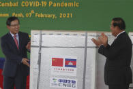 "Chinese ambassador to Cambodia Wang Wentian, left, presents a box loaded with COVID-19 vaccines to Cambodian Prime Minister Hun Sen during a handover ceremony at Phnom Penh International Airport, in Phnom Penh, Cambodia, Sunday, Feb. 7, 2021. Cambodia on Sunday received its first shipment of COVID-19 vaccine, a donation of 600,000 doses from China, the country's biggest ally. Beijing has been making such donations to several Southeast Asian and African nations in what has been dubbed ""vaccine diplomacy,"" aimed especially at poorer countries like Cambodia. (AP Photo/Heng Sinith)"
