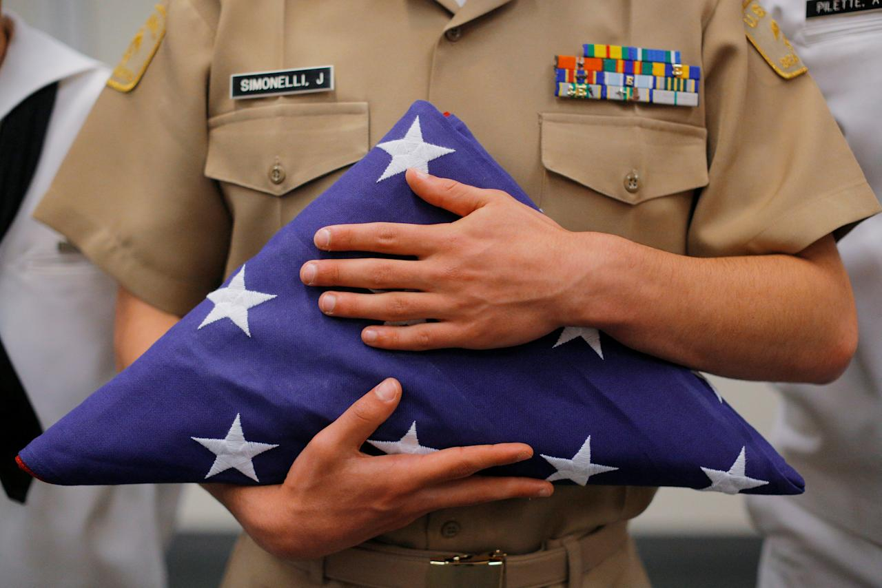 United States Naval Sea Cadet Corps Chief Petty Officer Jared Simonelli holds a folded U.S. flag, the first of 100 flags raised and lowered at the John F. Kennedy Presidential Library on the 100th anniversary of President Kennedy's birth, in Boston, Massachusetts, U.S., May 29, 2017.   REUTERS/Brian Snyder     TPX IMAGES OF THE DAY