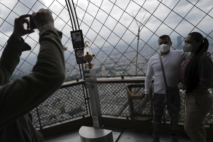 Visitors take photo with their phone from the third level during the opening up of the top floor of the Eiffel Tower, Wednesday, July 15, 2020 in Paris. The top floor of Paris' Eiffel Tower reopened today as the 19th century iron monument re-opened its first two floors on June 26 following its longest closure since World War II. (AP Photo/Francois Mori)