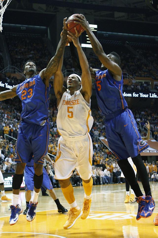 Tennessee forward Jarnell Stokes (5) battles for a rebound with Florida forward Chris Walker (23) and Florida guard Will Yeguete in the first half of an NCAA college basketball game on Tuesday, Feb. 11, 2014, in Knoxville, Tenn. (AP Photo/Wade Payne)