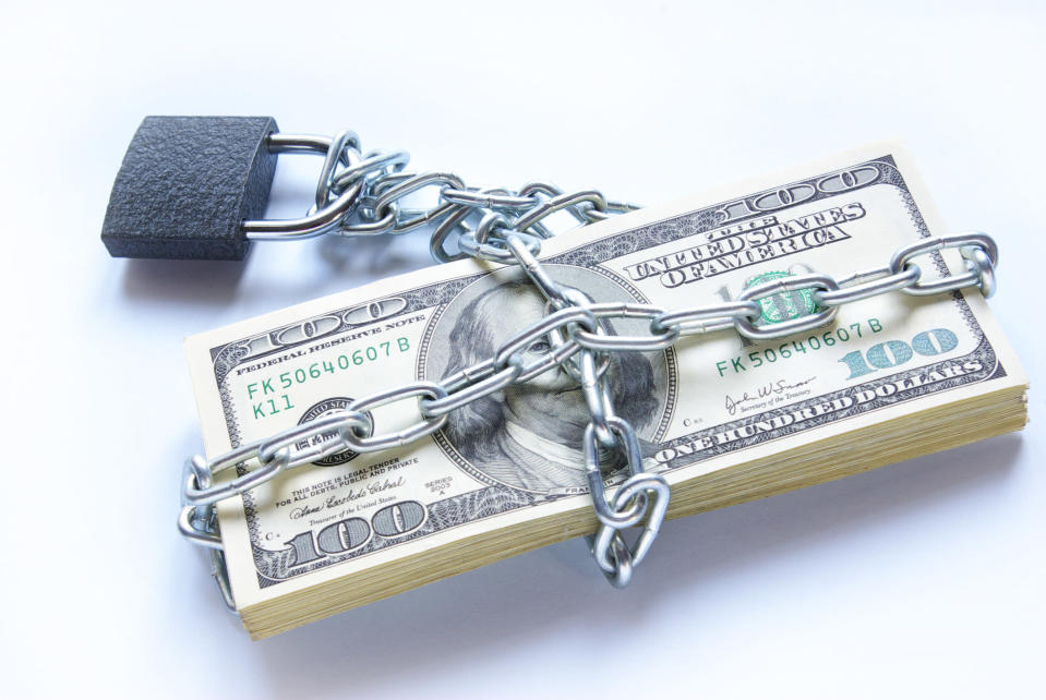 A neat stack of $100 bills wrapped up by chains and locked in place.
