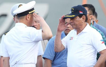 Philippine President Rodrigo Duterte returns the salute of a Chinese Navy officer as he tours a Chinese Naval ship during a visit to Davao