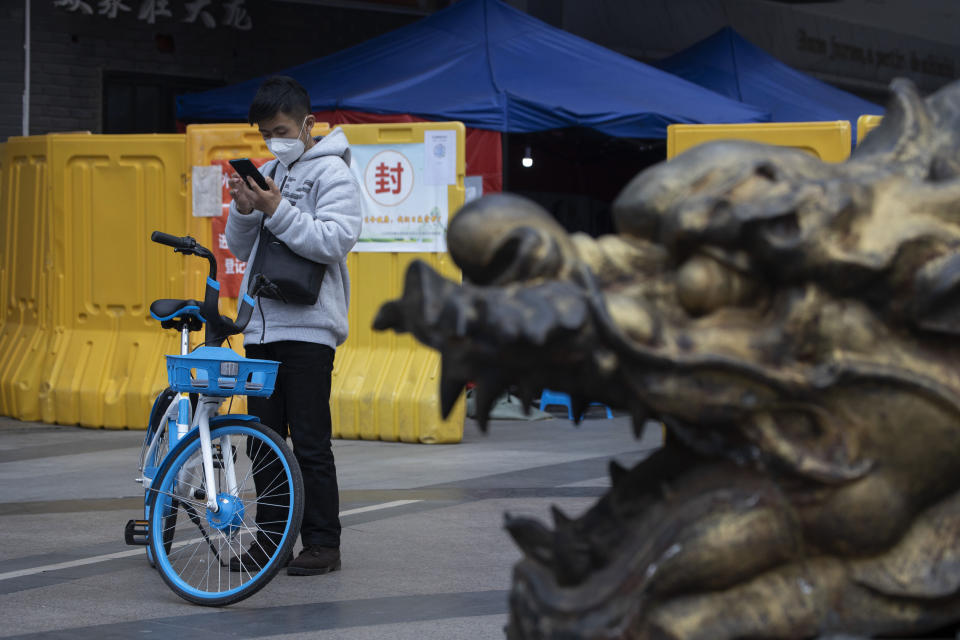 A resident wearing a mask against the coronavirus checks his phone near a sealed off community in Wuhan in central China's Hubei province on Sunday, April 5, 2020. The quarantine in the city which is the epicenter of China's coronavirus outbreak is to be formally lifted on Wednesday. (AP Photo/Ng Han Guan)