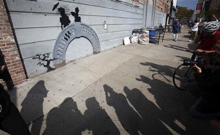 People take photos of a new art piece by British graffiti artist Banksy in the Brooklyn borough of New York, October 17, 2013. REUTERS/Carlo Allegri