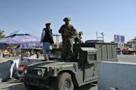 """A Taliban Badri fighter, part of a """"special forces"""" unit, stands guard on a Humvee at the main entrance gate of Kabul airport (AFP/WAKIL KOHSAR)"""