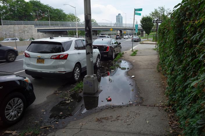 Puddles and cars are seen along a side road near a freeway.