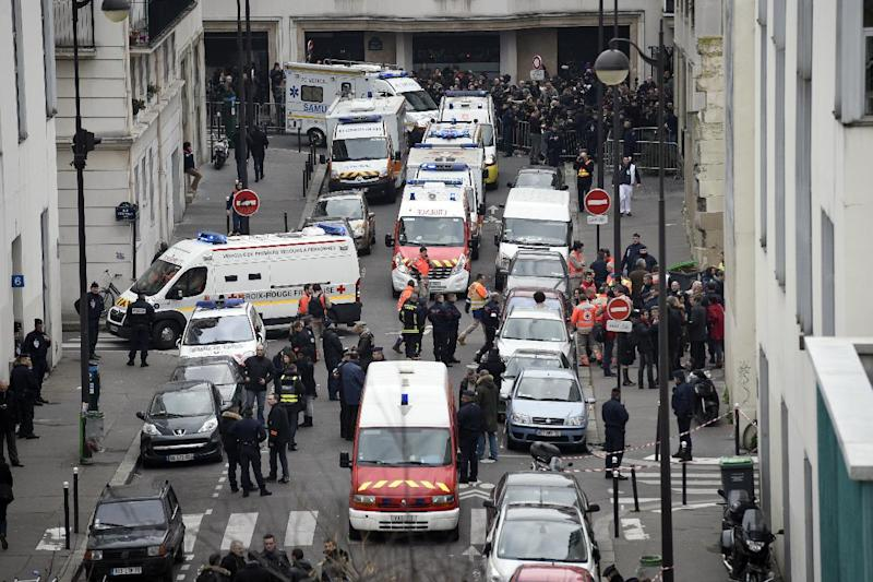 Firefighters, police officers and forensics experts pictured outside the offices of the French satirical newspaper Charlie Hebdo in Paris on January 7, 2015 (AFP Photo/Martin Bureau)