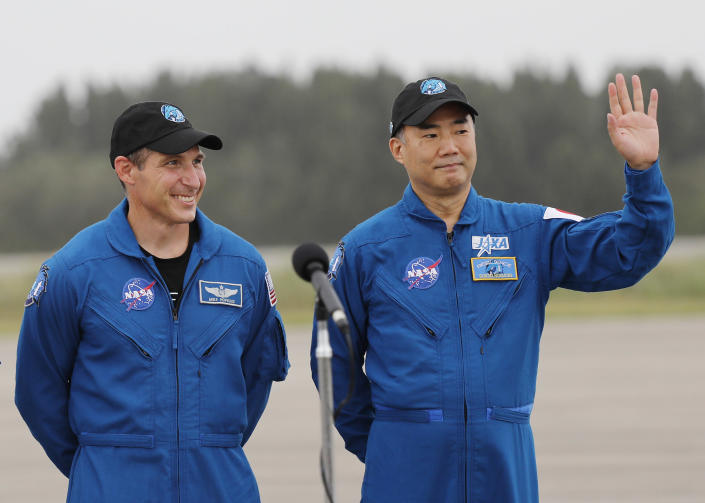 Astronaut Soichi Noguchi, right, of Japan, waves to the media as NASA Astronaut Michael Hopkins looks on during a news conference after they arrived at Kennedy Space Center, Sunday, Nov. 8, 2020, in Cape Canaveral, Fla. Four astronauts will fly on the SpaceX Crew-1 mission to the International Space Station scheduled for launch on Nov. 14, 2020. (AP Photo/Terry Renna)