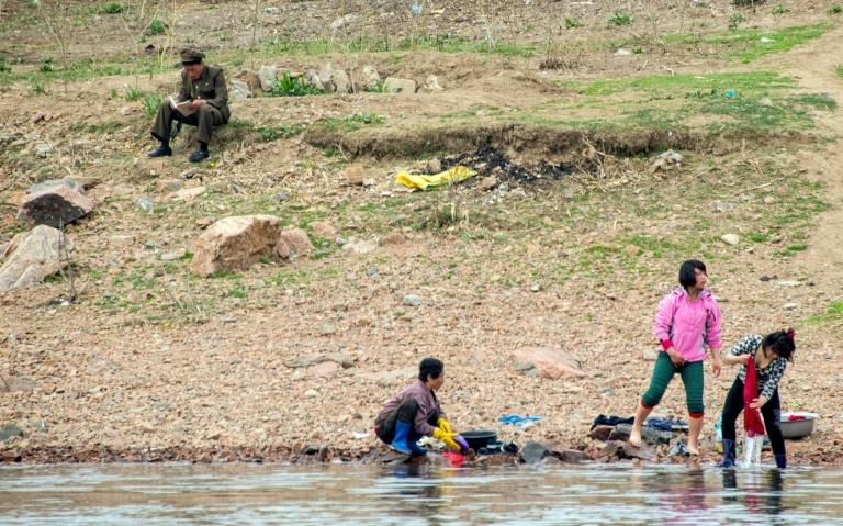 A North Korean soldier reads a book near women washing clothes in the Yalu border river on April 16, 2017