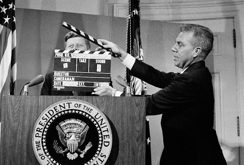 FILE - In this July 3, 1963 file photo, U.S. President John F. Kennedy stands at the lectern behind a production slate board during a television taping at the White House. In life and especially in death, Kennedy changed television forever. (AP Photo)