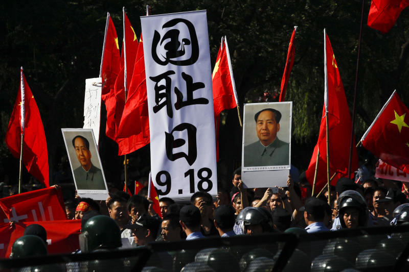 "Anti-Japan protesters hold portraits of the late Communist leader Mao Zedong, Chinese national flags, and a poster that reads: ""Sept. 18, National Humiliation Day,"" while marching on a street outside the Japanese Embassy in Beijing Tuesday, Sept. 18, 2012. The 81st anniversary of a Japanese invasion brought a fresh wave of anti-Japan demonstrations in China on Tuesday, with thousands of protesters venting anger over the colonial past and a current dispute involving contested islands in the East China Sea. (AP Photo/Alexander F. Yuan)"