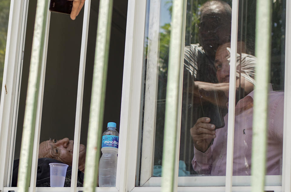 Patient Jose Silva, left, waits to be evacuated from the Bonsucesso Federal Hospital, which has a COVID-19 wing, as firefighters douse a blaze that broke out in Rio de Janeiro, Brazil, Tuesday, Oct. 27, 2020. According to the fire department, there were no casualties. (AP Photo/Silvia Izquierdo)