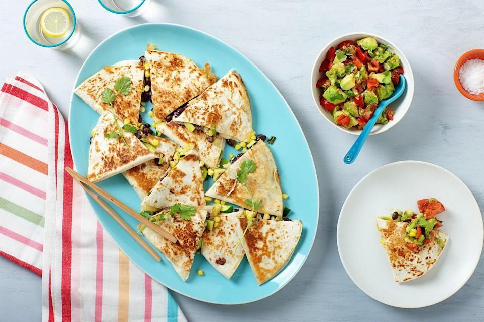 """Cooking corn this way adds a depth of flavor from the husk and keeps the kernels from drying out. Tossed together with zucchini and scallions, these quesadillas make for a super-satisfying vegetarian dinner. <a href=""""https://www.epicurious.com/recipes/food/views/grilled-corn-zucchini-and-black-bean-quesadillas-56389624?mbid=synd_yahoo_rss"""" rel=""""nofollow noopener"""" target=""""_blank"""" data-ylk=""""slk:See recipe."""" class=""""link rapid-noclick-resp"""">See recipe.</a>"""
