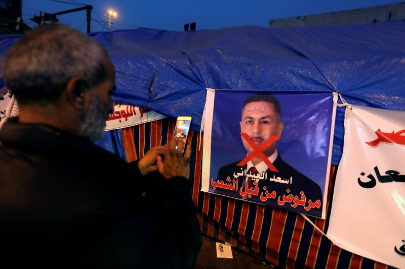 An Iraqi demonstrator takes a photo of a poster of Asaad al-Edani, Basra governor and a candidate for the prime minister office during ongoing anti-government protests in Baghdad