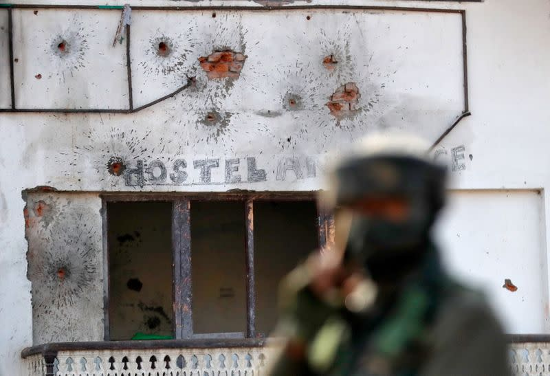 Bullet holes are seen on the wall of a house next to a soldier standing guard, after a gun battle between Indian army soldiers and suspected militants in Hokarsar