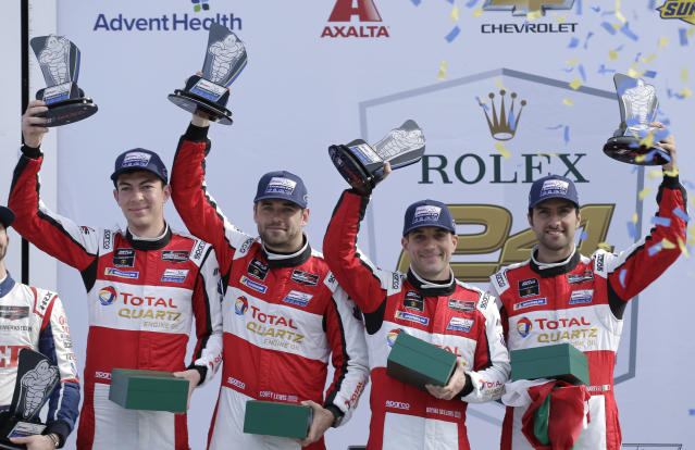 GT Daytona class winners Madison Snow, Corey Lewis, Bryan Sellers and Andrea Caldarelli hold up their trophies in Victory Lane after the Rolex 24-hour auto race at Daytona International Speedway, Sunday, Jan. 26, 2020, in Daytona Beach, Fla. (AP Photo/Terry Renna)