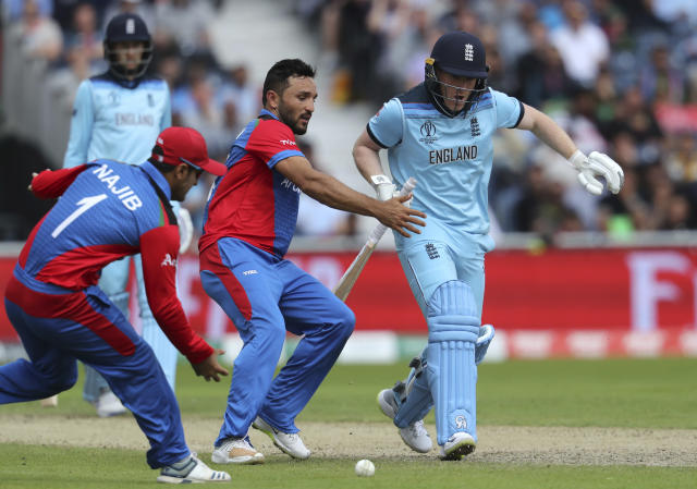 Afghanistan's captain Gulbadin Naib, center, and teammate Najibullah Zadran, left, attempt to run-out England's captain Eoin Morgan, right, during the Cricket World Cup match between England and Afghanistan at Old Trafford in Manchester, England, Tuesday, June 18, 2019. (AP Photo/Rui Vieira)