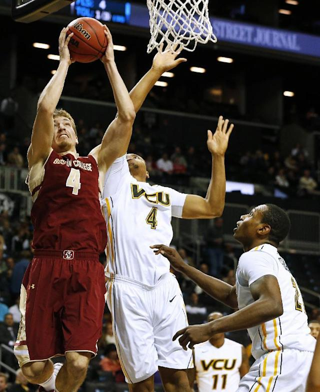 Boston College's Eddie Odio, left, takes a shot as VCU's Terrance Shannon, second from left, defends during the first half of an NCAA college basketball game Saturday, Dec. 28, 2013, in New York. (AP Photo/Rich Schultz)